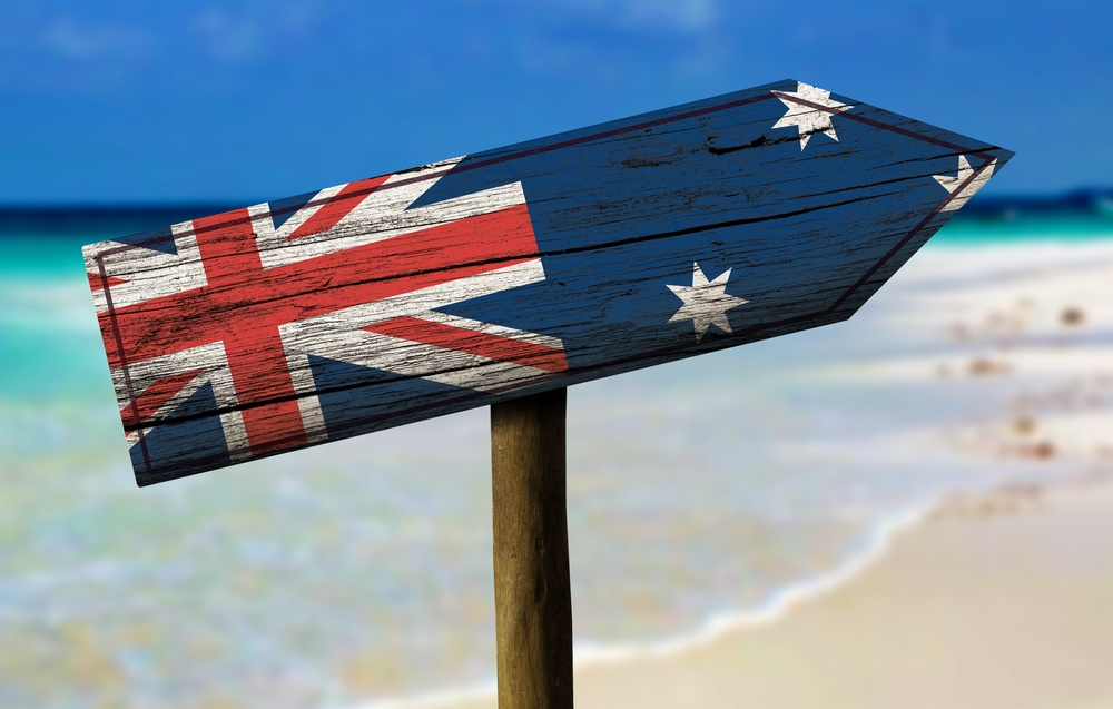 Australia flag wooden sign with a beach on background - Oceania