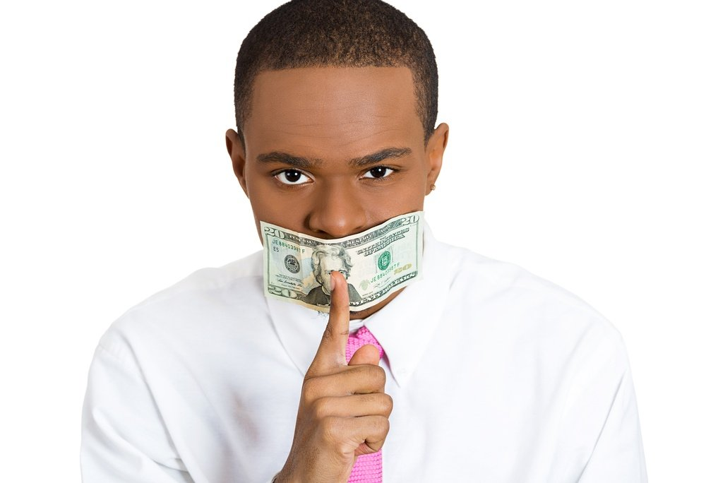 Closeup portrait young corrupt man with cash, dollar, money bill taped to mouth, showing shhh sign, isolated white background. Bribery concept in politics, business, diplomacy. Life perception