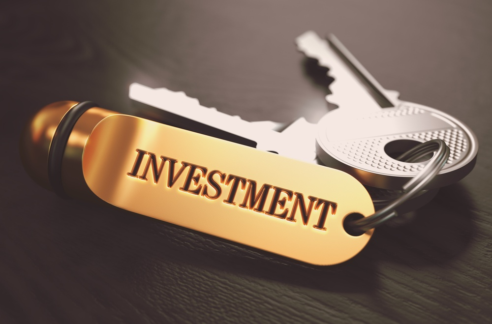 Keys with Word Investment on Golden Label over Black Wooden Background. Closeup View, Selective Focus, 3D Render. Toned Image.