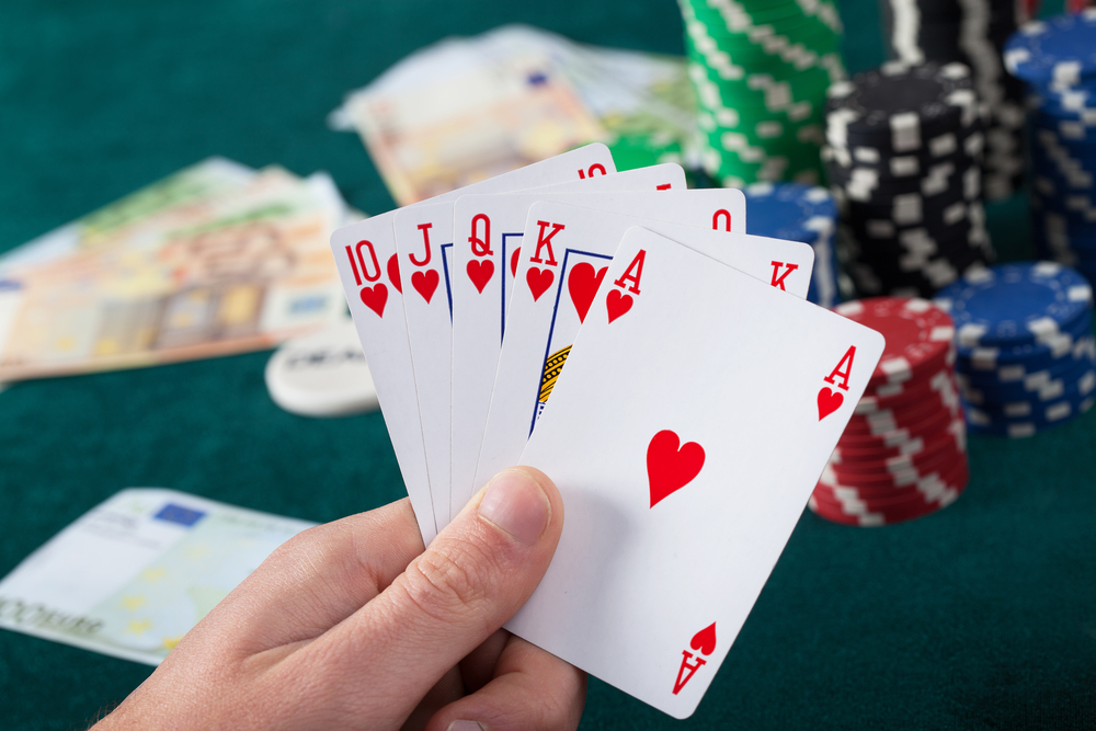 Mans hand holding royal flush in poker game