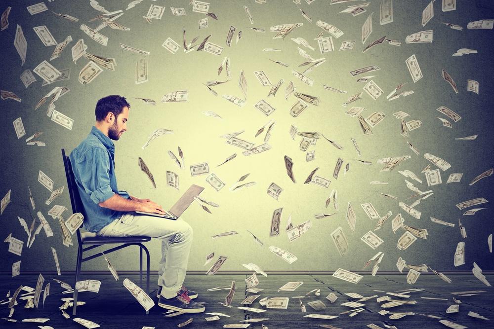 Young man using a laptop building online business making dollar bills cash falling down. Beginner IT entrepreneur under money rain. Success economy concept